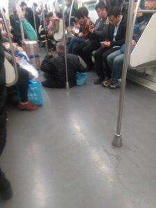 地下鉄車内の床に座って二胡を弾く老人